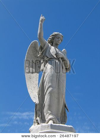 Detail of winged angel statue against blue sky