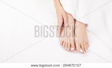 Female Feet On Towel. Nails Getting A Fresh And Accurate Look During A Pedicure Procedure.