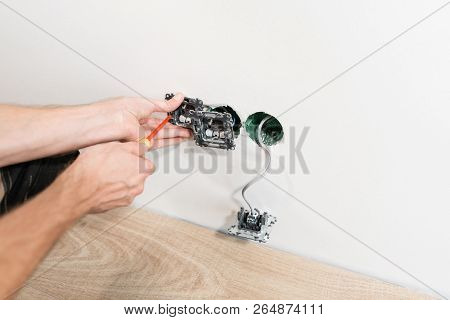 Electrician Connects The Sockets To The Electrical Wires On Wall In White Room. Screwdriver, Close-u