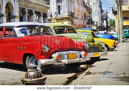 Detail of colorful group of vintage american cars parked in a street of Old havana