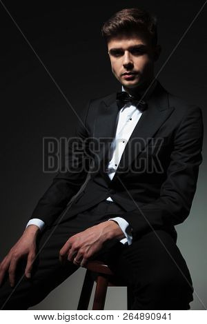 elegant young man in tuxedo sits on wooden chair on grey background while resting hand on thigh