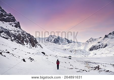 Hiker With Red Backpack Walking Around Snowy Mountain At Purple Sky Background. Freedom Of Trekking