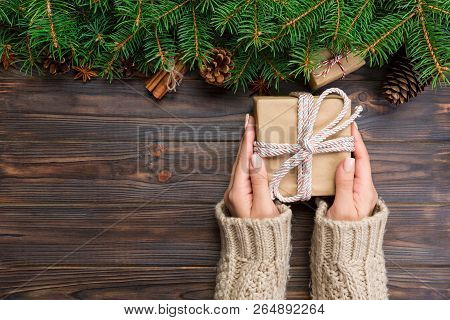 Woman Hands Give Wrapped Christmas Handmade Present In Paper With Pink Ribbon. Present Box On Holida