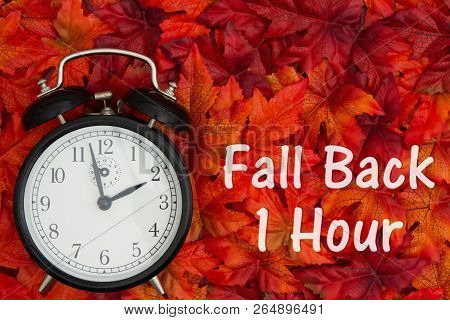Daylight Savings Time Message, Some Fall Leaves And Retro Alarm Clock With Text Fall Back 1 Hour