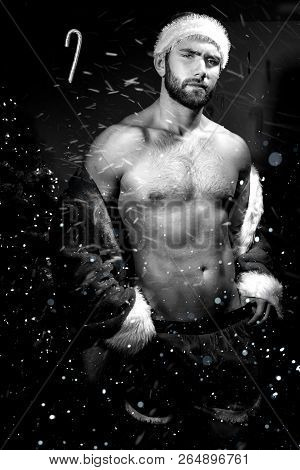 Good Looking Male Santa With Open Jacket, Revealing Chest And Pecs With Christmas Tree In Background