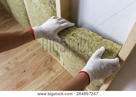Close-up Of Worker Hands In White Gloves Insulating Rock Wool Insulation Staff In Wooden Frame For F