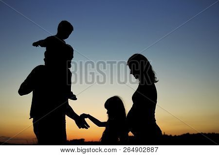Silhouette Of A Happy Pregnant  Family With Children