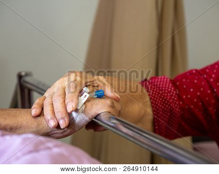 Wife Visiting Husband In Hospital. Senior Couple Holding Hands On Hospital Bed For Hospitalization F