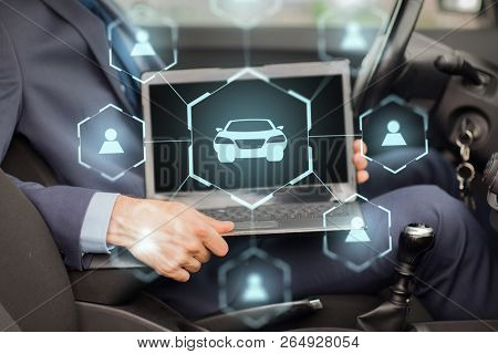 business, transportation and future technology concept - close up of businessman hand with transparent laptop computer and virtual car sharing icons