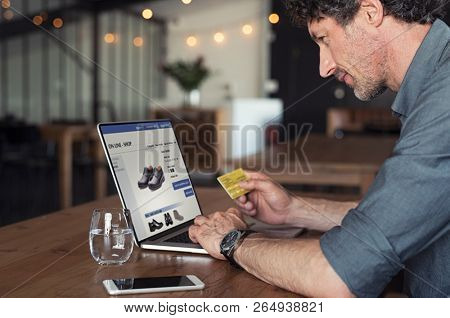 Senior businessman using debit card to make online transaction using laptop. Mature business man doing shopping online banking. Man making online payment with credit card and laptop.