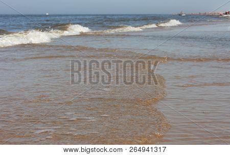 Waves With Whitecaps Flood The Sandy Beach