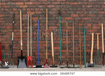Selection of hardware tools lined up vertically against a red brick wall. poster