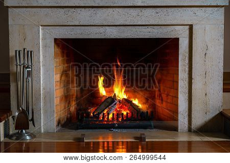 Wood Burning In A Cozy Fireplace At Home In Interior. Fireplace As A Piece Of Furniture. Christmas N