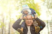 Shot of a happy senior man smiling looking away his grandson hugging him from behind copyspace relax family love people children retirement vitality lifestyle parenting childhood values weekend poster