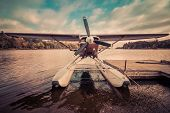 Seaplane docked at the shore in Long Lake, NY, awaiting leaf-peepers and adventure seekers, retro split tone poster