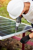 Close-up of professional technician working with screwdriver connecting solar photo voltaic panel to metal platform on warm sunny summer day. Stand-alone exterior solar panel system installation. poster