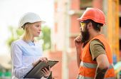 Discuss progress project. Construction project inspecting. Safety inspector concept. Woman inspector and bearded brutal builder discuss construction progress. Construction site safety inspection poster