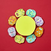 Handcraft paper Calaveras attributes of the Mexican holiday Calaca are decorated with a round yellow frame on a red background with space for text. Flat lay poster