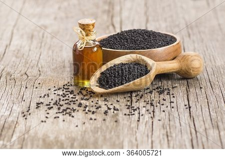 Glass Bottle Of Black Cumin Seeds Essential Oil , Nigella Sativa In Spoon On Wooden Background. Orga
