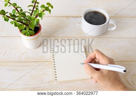 Copy Space On A Spring Notepad. Woman Hand Holding Ballpoint Pen And Going To Write In Paper Notepad