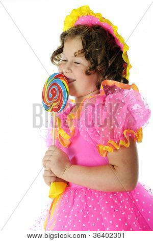 A young elementary girl playing Shirley Temple in her colorful hat and frilly dress, swooning over her giant lollipop.  On a white background.