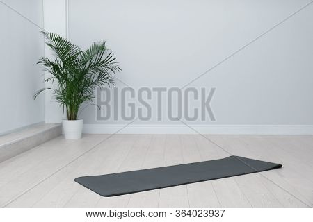 Unrolled Black Yoga Mat On Floor In Room. Space For Text