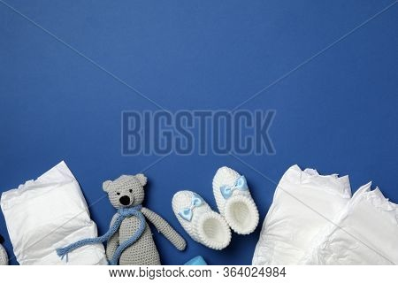 Diapers And Baby Accessories On Blue Background, Flat Lay. Space For Text