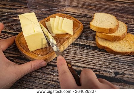 Someone Cuts Some Butter With A Knife From A Piece Of Butter In A Wooden Butter Dish, Slices Of Chee