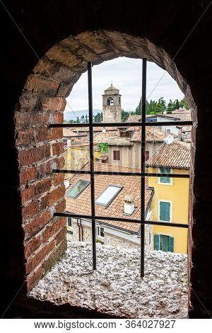 Sirmione, Italy - October 01, 2015 : City View From The Window With A Metal Grill Of The Castello Sc