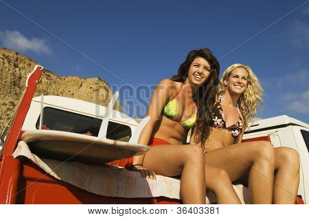 Low angle view of two cheerful women sitting on a crew cab