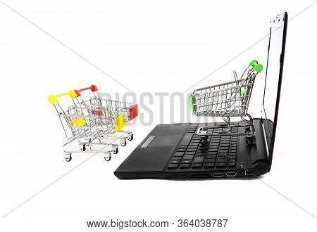 Three Empty Miniature Shopping Carts Stand Close To A Black Laptop Isolated On White. E-commerce Con