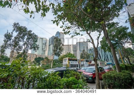 Hong Kong - 2020: Lum Fung Street, Cars, Buses, Trees And Office Building - Enterprise Square, Centr