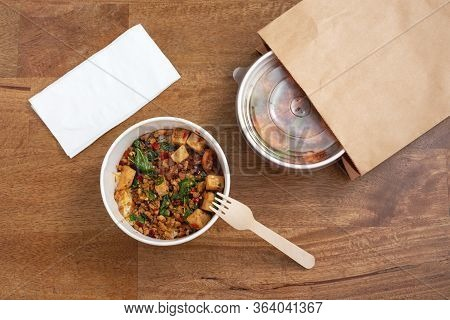Takeaway Asian Food Delivery. Stir Fried Pork And Basil With Rice In Paper Box On Wooden Background