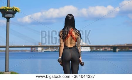 Backside View Of Fit Woman With Dumbbells Outdoors