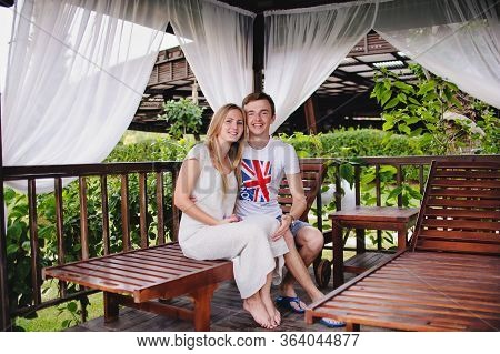 Happy Young Couple Embrace In Gazebo In Nature. Sits On Bed In Wooden Installations For Recreation.