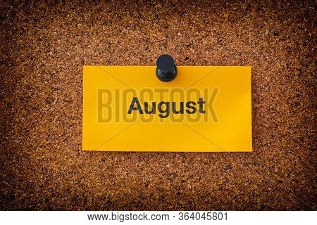 August Written On A Yellow Piece Of Paper That Is On A Bulletin Board. Close Up.