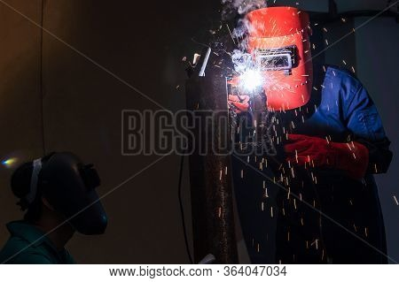 The Welder Is Welding The Steel With An Electric Welding Machine Inside The Factory.