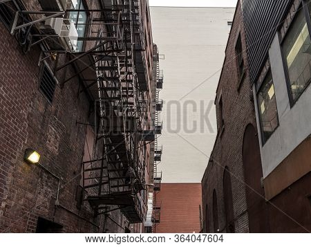 Fire Escape Stairs And Ladder, In Metal, On A Typical North American Old Brick Building From The Old