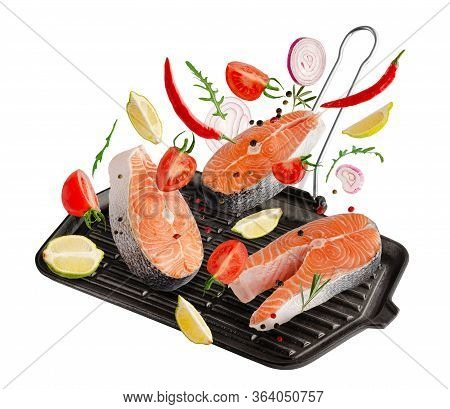 Raw Steaks Of Salmon Or Trout Fish With Spices And Herbs Falling On Grill Pan Isolated On White Back