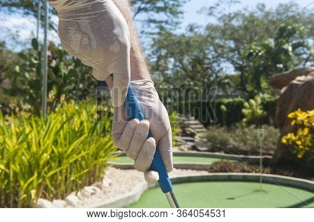 Gloved Hands Holding A Blue Mini Golf Club In The Sun
