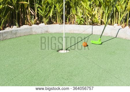 Green Mini Golf Club Puts And Orange Ball Towards A Hole On Green Turf