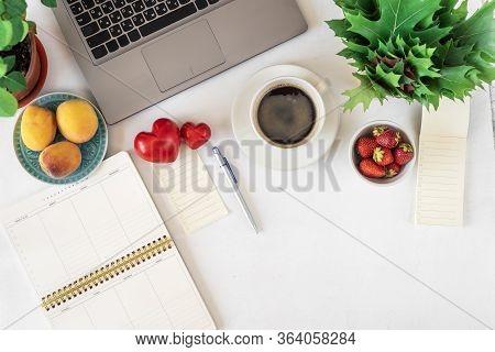 Desktop With Laptop, Weekly Notebook, Pen, Coffee, Fruit, Flowers, Top View