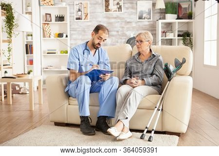 Male Caregiver Taking Notes On Clipboard While Talking With Senior Woman In Nursing Home.