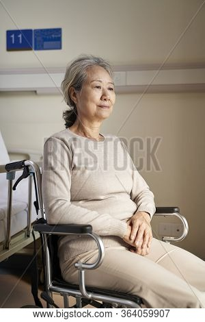 Asian Old Woman Sitting In Wheelchair In Her Room In Nursing Home With Blank Facial Expression