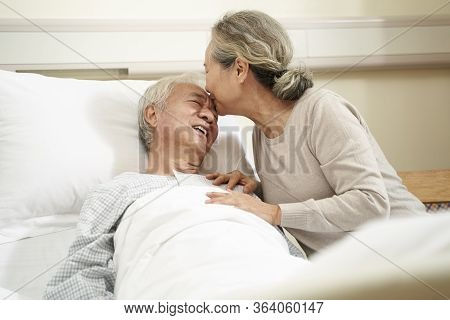 Senior Asian Woman Kissing Husband On The Forehead In Hospital Ward