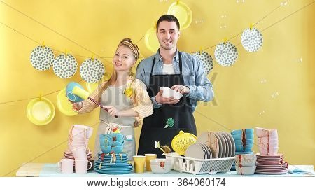 Attractive Couple In Love In A Good Mood Is Engaged In Household Chores, Washing Up Dirty Dishes Aft