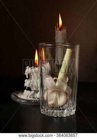 Retro Country Style Still Life With Garlic Bulb In Glass Beaker And Two Candlesticks With Burning Ca