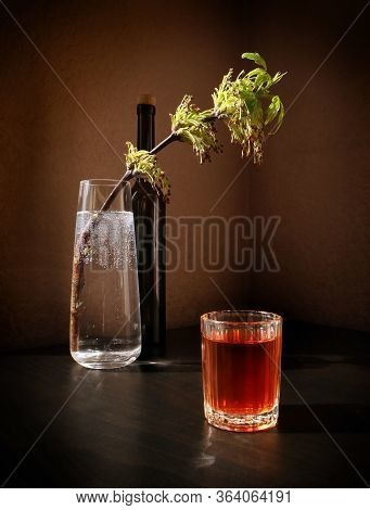 Still Life With Flowering Spring Twig Of Ash-tree With Young Leaves In A Glass Vase, Black Bottle An