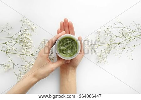 Young Female Hands Hold A Jar Of Green Natural Cream For Face Or Body. Organic Natural Skincare Prod