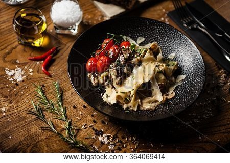 Black Angus Pappardelle Pasta With Beef, Champignon And Parmegano Cheese On A Black Plate. Delicious